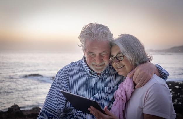 해변에서 황혼에 앉아 같은 태블릿을 보고 재미 수석 행복 한 커플. 기술을 즐기는 은퇴한 사람들, 바다 너머의 수평선