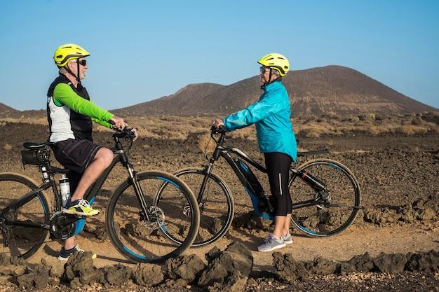 電動自転車、electrobikeとの屋外遠足のシニア幸せなカップル。アクティブな退職した高齢者の健康の概念