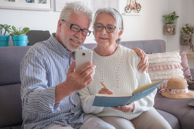 Senior happy couple sitting on sofa at home using mobile phone