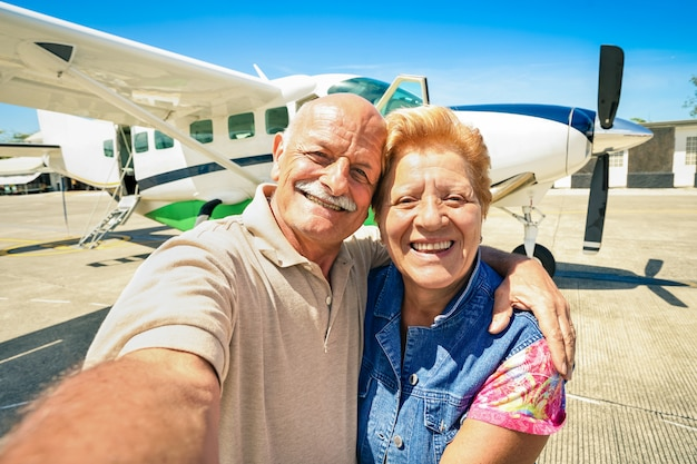 Senior happy couple taking selfie with private ultralight plane for tour around the world