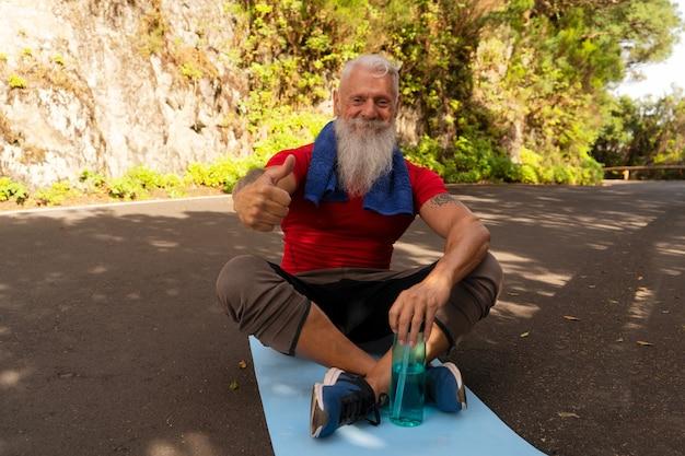 Старший счастливый улыбающийся мужчина с белой бородой делает упражнения на природе