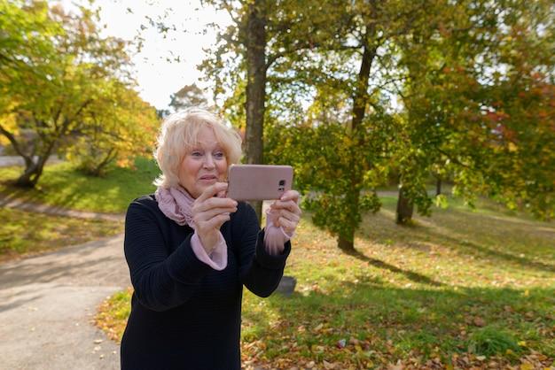 静かでリラックスできる自然公園の小道で携帯電話で写真を撮っている間笑顔のシニア幸せな女性