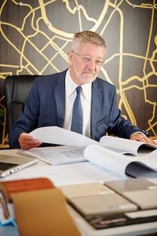Старший руководитель архитектурного бюро проверяет документы с планами зданий и планами строительства.