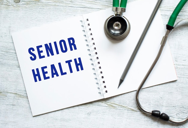 Senior health is written in a notebook on a light wooden table next to pencil and a stethoscope