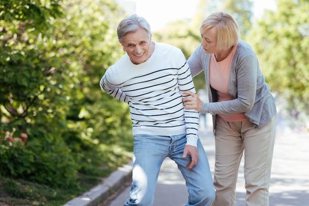 病気の男性を気遣い、屋外を歩きながら彼をサポートする年配の親切な老婆