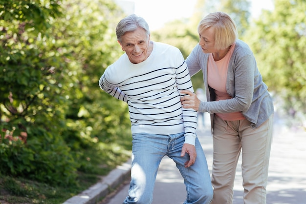 Senior helpful aged woman caring about ill man and supporting him while walking outdoors