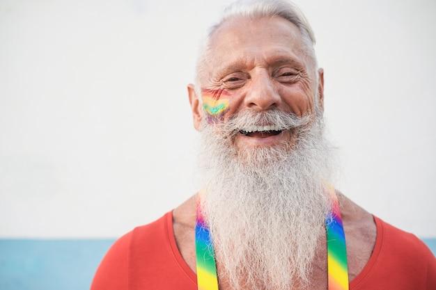 Senior hipster gay man smiling on camera