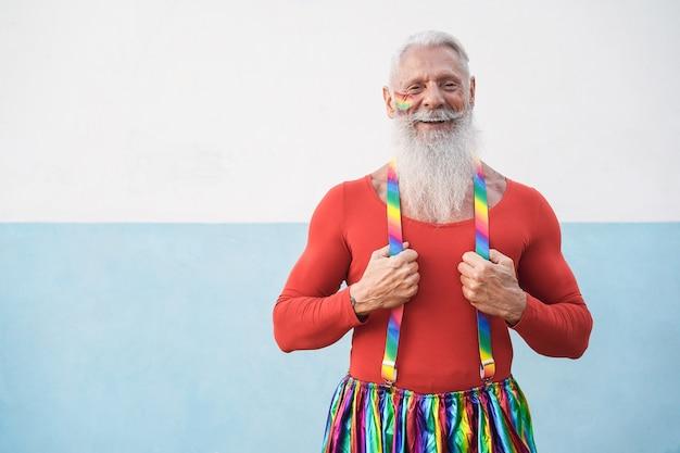 屋外のカメラで笑っているシニアヒップスターゲイ男性-顔に焦点を当てる