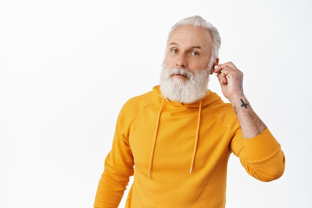 Senior hipster man take-off earbud to hear you. old stylish guy looking questioned, cant hear you while listening music in headphones, white wall