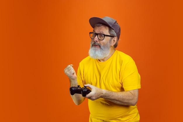 Старший хипстерский мужчина, использующий гаджеты устройств на оранжевом фоне, технологий и радостного пожилого образа жизни