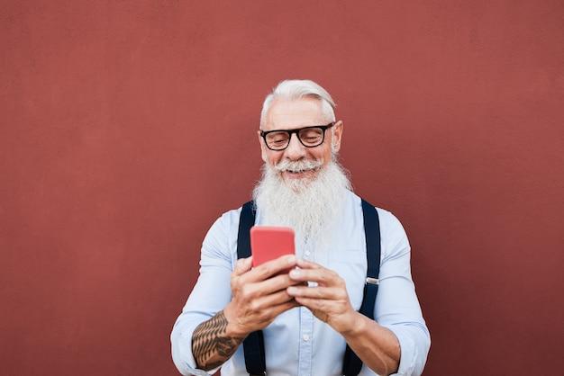 백그라운드에서 붉은 벽과 야외에서 휴대 전화를 사용하는 수석 힙 스터 남자-얼굴에 초점
