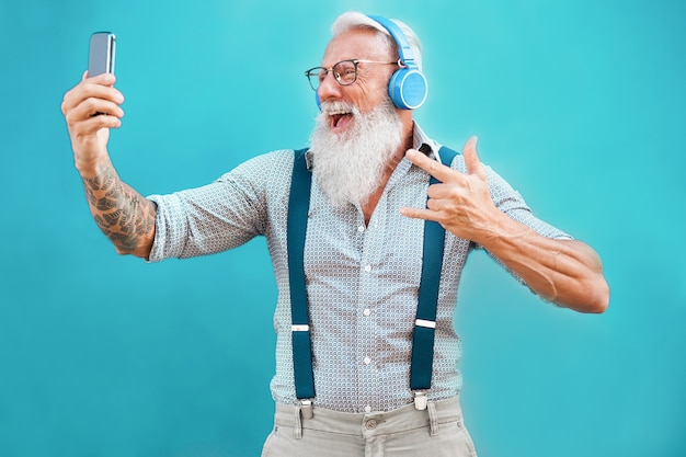 Старший хипстерский человек, использующий приложение для смартфонов для создания плейлиста с рок-музыкой