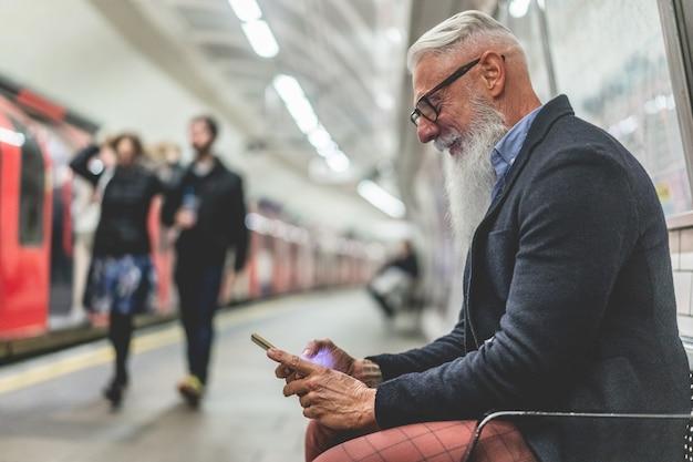 Старший хипстерский человек, использующий смартфон в подземном метро - мода зрелого человека, весело проводящего время с технологическими тенденциями, ждущими его поезда - радостная пожилая концепция образа жизни - основное внимание на руке крупным планом