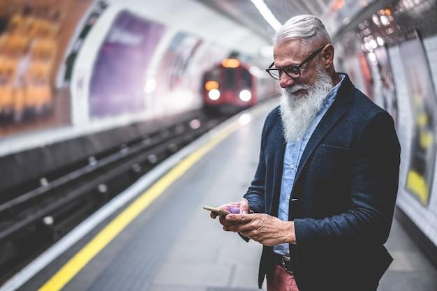 Старший хипстерский человек, использующий смартфон в подземном метро - мода зрелого человека, весело проводящего время с технологическими тенденциями, ожидающими его поезда - радостная концепция образа жизни пожилых людей - основное внимание на лице