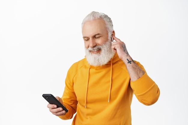 Senior hipster put earphone in ear and smiling, looking at playlist on mobile phone, white wall
