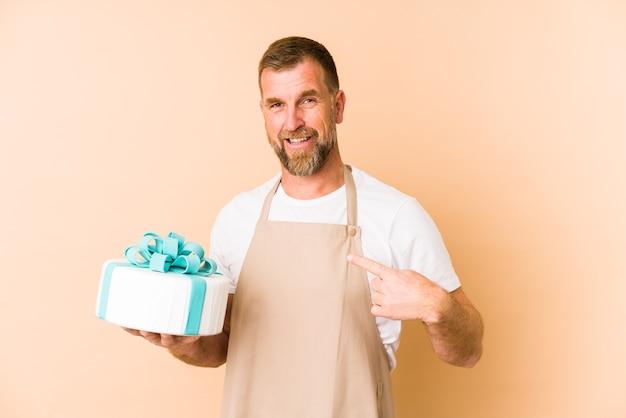 シャツのコピースペースを手で指しているベージュの壁の人に分離されたケーキを保持しているシニア、誇りと自信