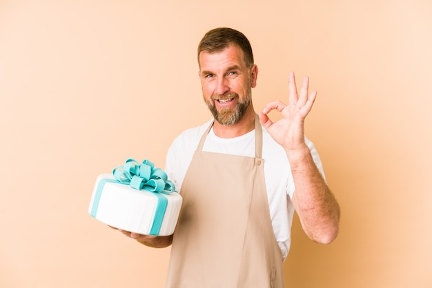 Senior holding a cake on beige wall cheerful and confident showing ok gesture.