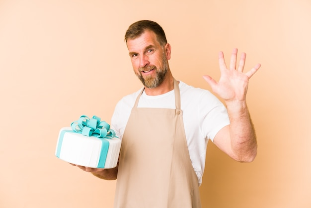 Senior holding a cake isolated on beige wall smiling cheerful showing number five with fingers.