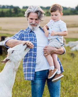 Senior holding ragazzino all'azienda agricola