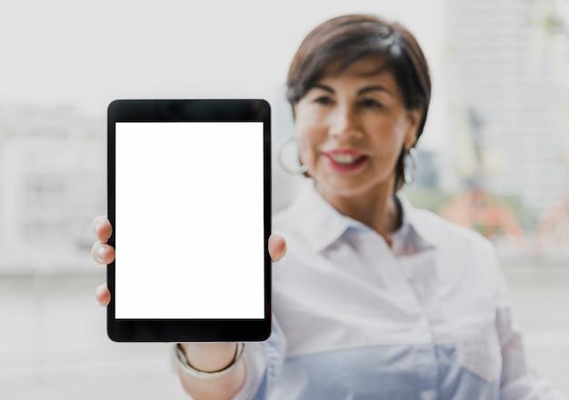Senior holding a mockup tablet