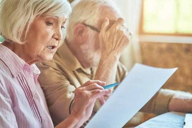 집에서 재무 서류를 분석하는 수석 남편과 아내