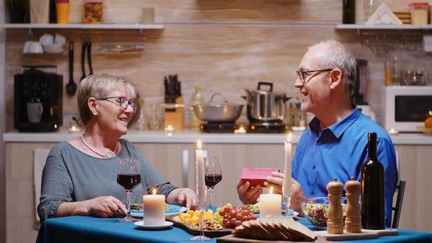 부엌에서 낭만적인 저녁 식사를 하는 동안 노인 아내에게 선물을 주는 수석 남편. 행복한 노인 부부는 집에서 함께 식사를 하고, 식사를 즐기고, 기념일을 축하하고, 깜짝 홀리를 축하합니다.