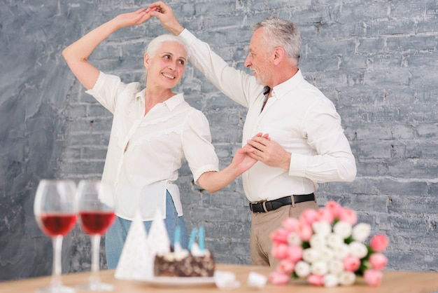 Senior husband and wife dancing at birthday party