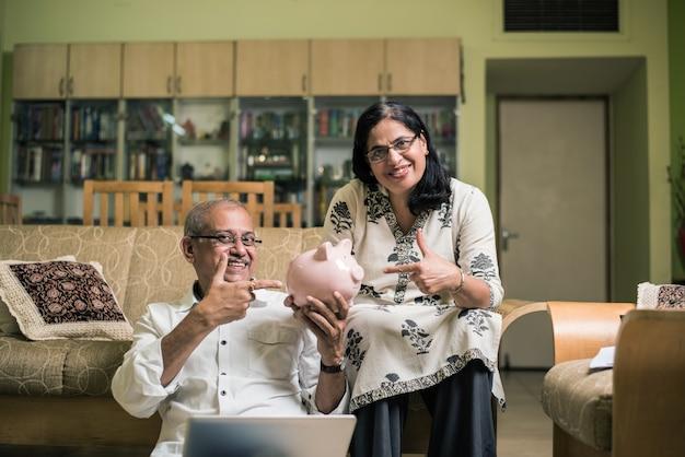 수석 인도 아시아 부부 회계, 가정 재정을 하고 집에서 소파 소파나 탁자에 앉아 있는 동안 노트북, 계산기, 돈을 돼지 저금통으로 확인하는 청구서 확인