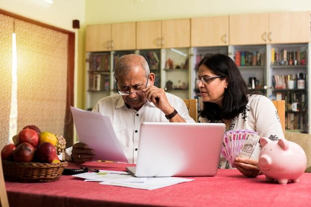 シニアインドのアジア人カップルの会計、家計簿の作成、自宅のソファのソファやテーブルに座っている間、貯金箱でラップトップ、計算機、お金を使って請求書をチェックする