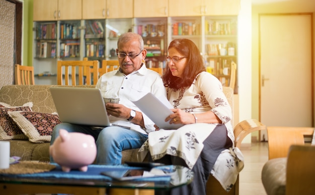 Senior indian asian couple accounting, doing home finance and checking bills with laptop, calculator and money also with piggy bank while sitting on sofa couch or table at home