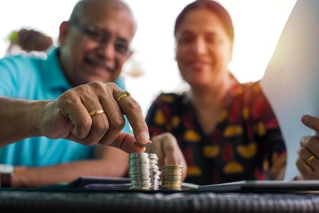 한 줄로 늘어선 동전 더미를 배열하거나 걸고 있는 인도 아시아 노인 부부, 선별적인 집중