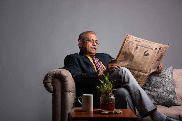 Старший индийский азиатский руководитель или бизнесмен в костюме и галстуке, читающий новости в газете или на смартфоне, сидя на диване или диване с кофейной кружкой