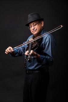 기타 또는 바이올린과 같은 현악기로 연주하거나 포즈를 취하는 인도 아시아 미남 남성, 검은 배경 위에 서 있거나 소파나 소파에 앉아