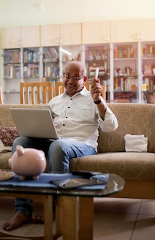 집에서 돈, 노트북, 계산기를 가지고 회계하는 인도 아시아 노인