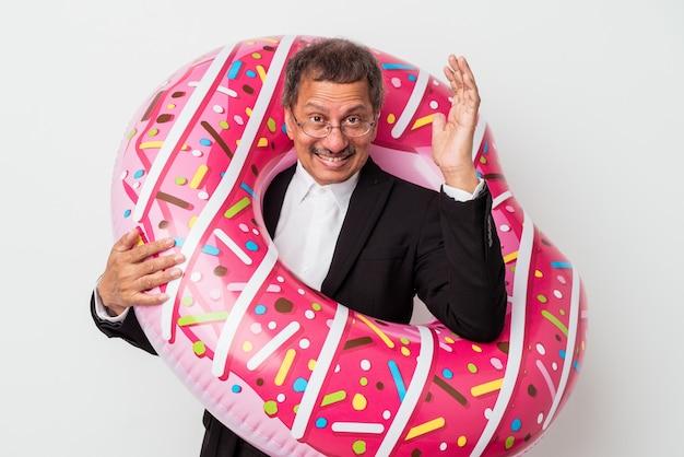 흰색 배경에 격리된 부풀릴 수 있는 도넛을 들고 있는 인도 사업가는 즐거운 놀라움과 흥분, 손을 들고 있습니다.
