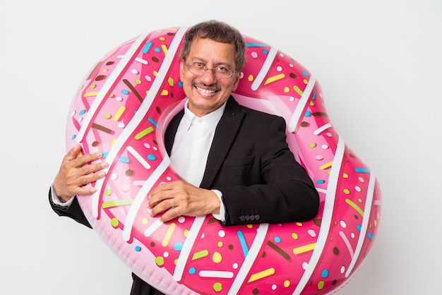 Senior indian business man holding inflatable donut isolated on white background happy, smiling and cheerful.