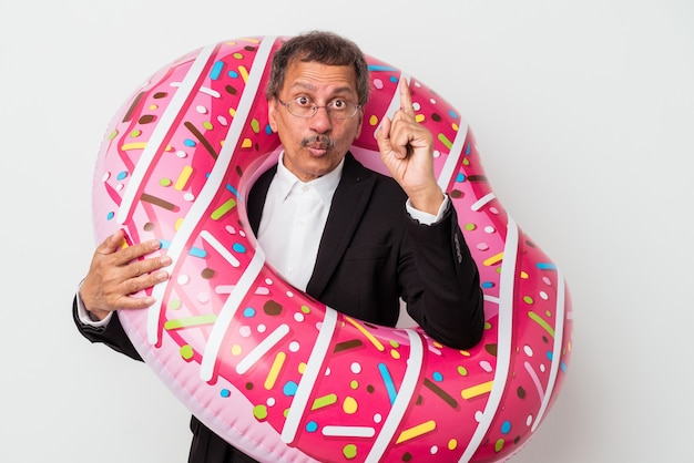 Senior indian business man holding inflatable donut isolated on white background having some great idea, concept of creativity.