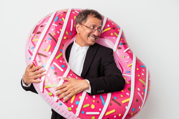 Senior indian business man holding inflatable donut isolated on white background looks aside smiling, cheerful and pleasant.