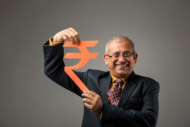 灰色の背景の上に孤立して立って、紙で作られたルピー記号の切り抜きを保持しているシニアインドのビジネスマン