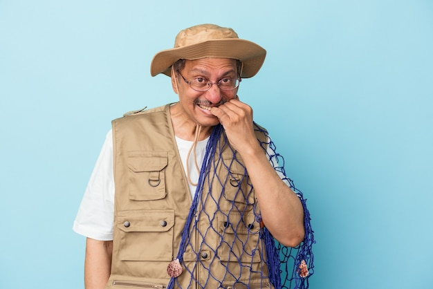 Senior indian fisherman holding net isolated on blue background biting fingernails, nervous and very anxious.