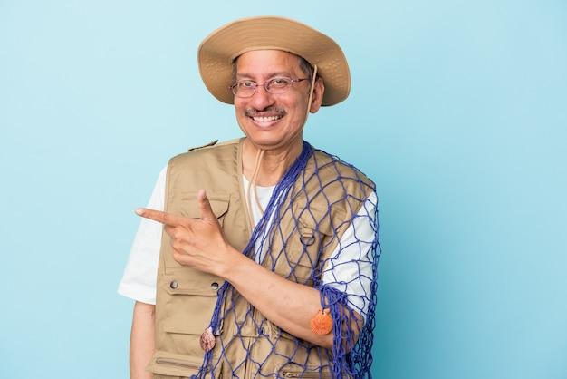 푸른 배경에 격리된 그물을 들고 있는 인도의 수석 어부는 웃고 옆으로 가리키며 빈 공간에 뭔가를 보여주고 있습니다.