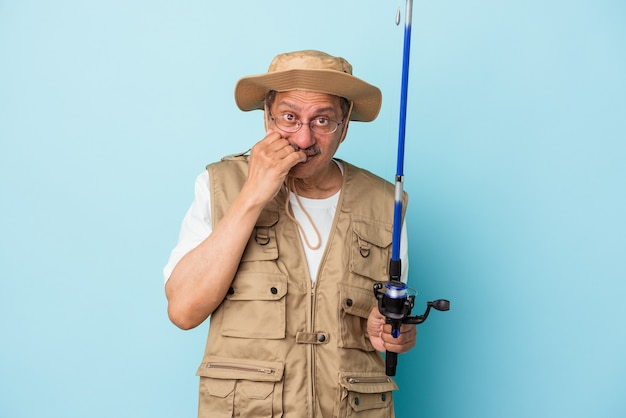 Senior indian fisherman holding rod isolated on blue background biting fingernails, nervous and very anxious.