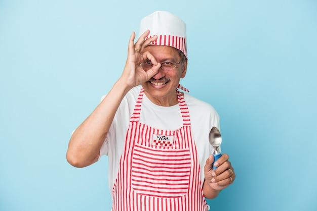 青い背景で隔離のスクープを保持しているシニアインドのアイスクリームの男は、目に大丈夫なジェスチャーを維持して興奮しました。