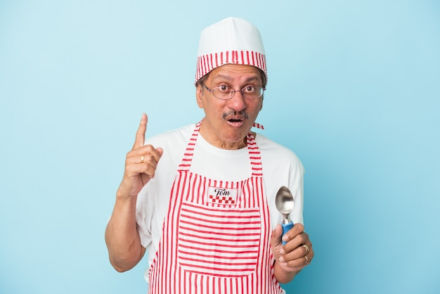 いくつかの素晴らしいアイデア、創造性の概念を持っている青い背景で隔離のスクープを保持しているシニアインドのアイスクリームの男。