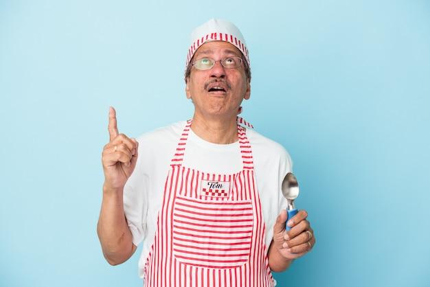 口を開けて逆さまを指している青い背景で隔離のスクープを保持しているシニアインドのアイスクリームの男。