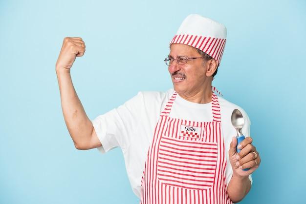 勝利、勝者の概念の後に拳を上げる青い背景で隔離のスクープを保持しているシニアインドのアイスクリームの男。