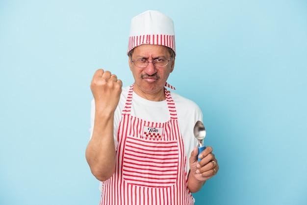 カメラに拳、攻撃的な表情を示す青い背景で隔離のスクープを保持しているシニアインドのアイスクリームの男。 Premium写真