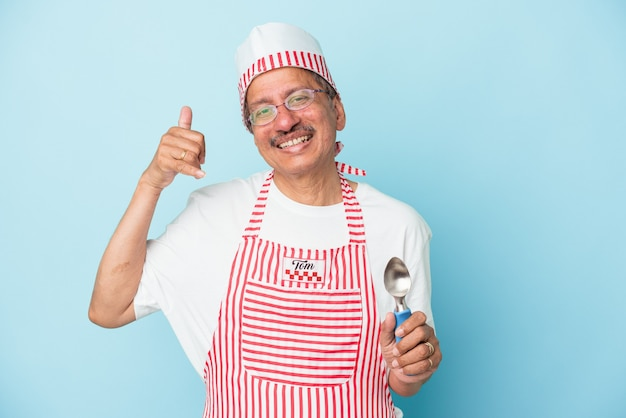 Senior indian ice cream man holding a scoop isolated on blue background showing a mobile phone call gesture with fingers.