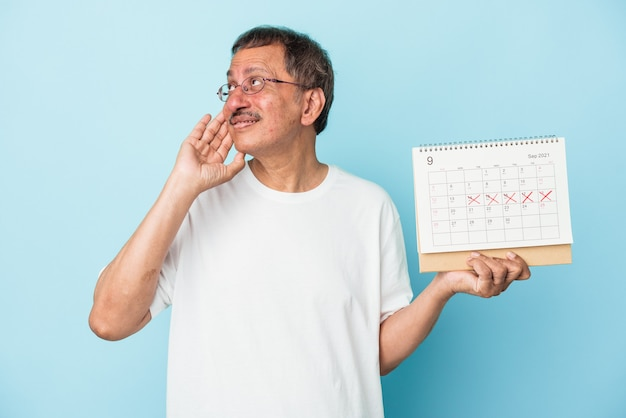 Senior indian man holding a calendar isolated on blue background looking sideways with doubtful and skeptical expression.