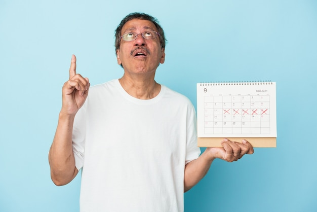 Senior indian man holding a calendar isolated on blue background pointing upside with opened mouth.